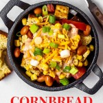 a serving of cornbread salad in a mini cast iron skilled with a spoon and yellow napkin on a table.