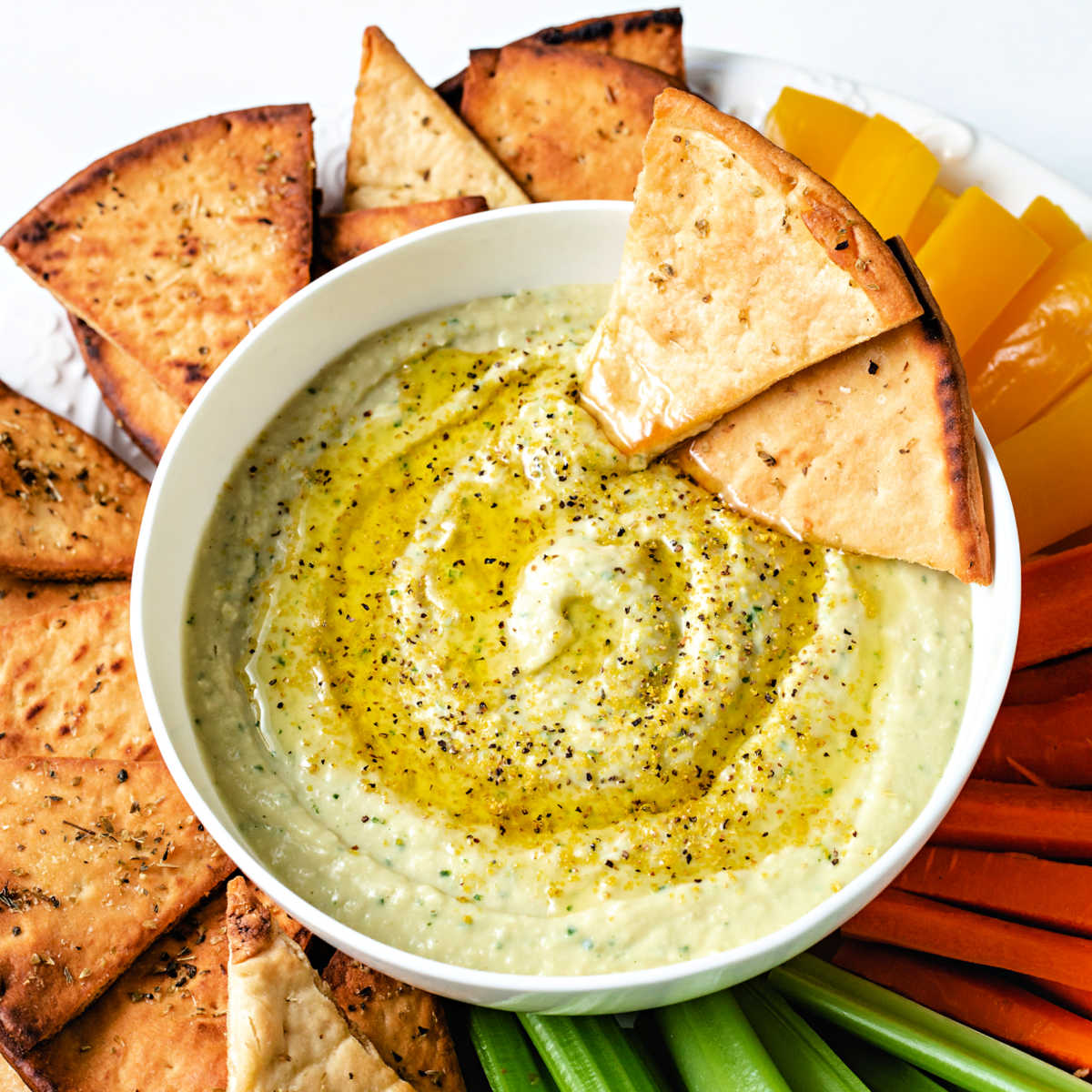 a bow of white bean hummus garnished with lemon pepper seasoning and olive oil on a platter with pita chips and veggie sticks.