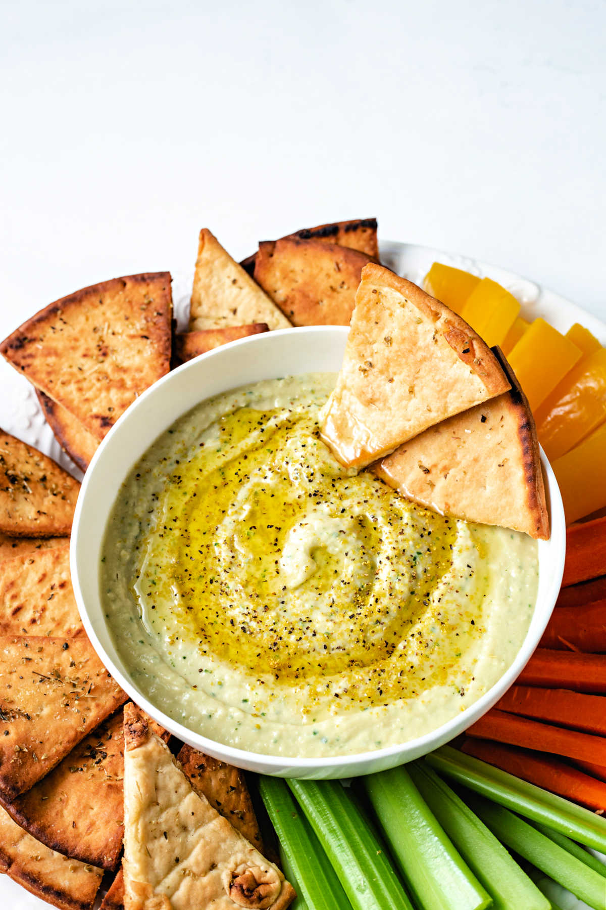 two baked pita chips nestled into a bowl of white bean hummus.