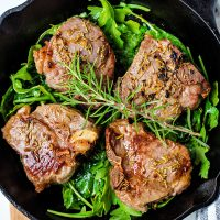 broiled lamb chops on a bed of arugula in a cast iron pan and garnished with a sprig of rosemary.
