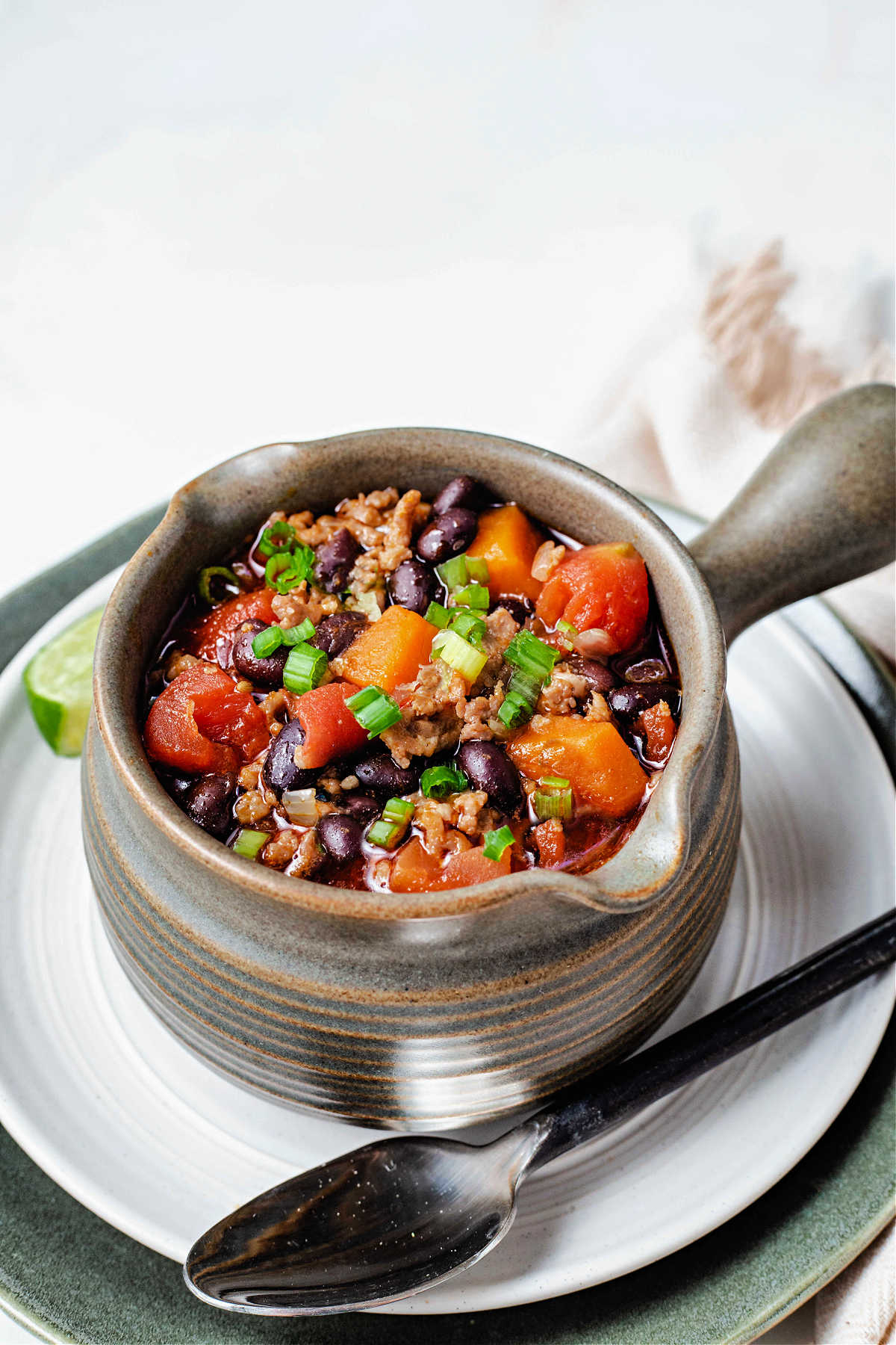 a soup mug filled with black bean and sweet potato chili  sitting on a white plate with a spoon laying to the side.