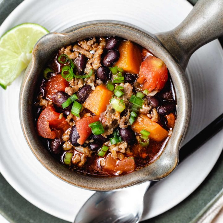 top down view of a soup mug filled with black bean and sweet potato chili sitting on a white plate with a spoon laying to the side.