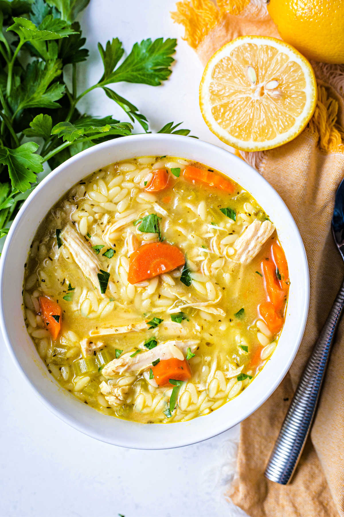 a bowl of lemon chicken orzo soup on a table with parsley and lemon.