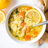 lemon chicken orzo soup in a white bowl with a slice of lemon and a spoon on a table.