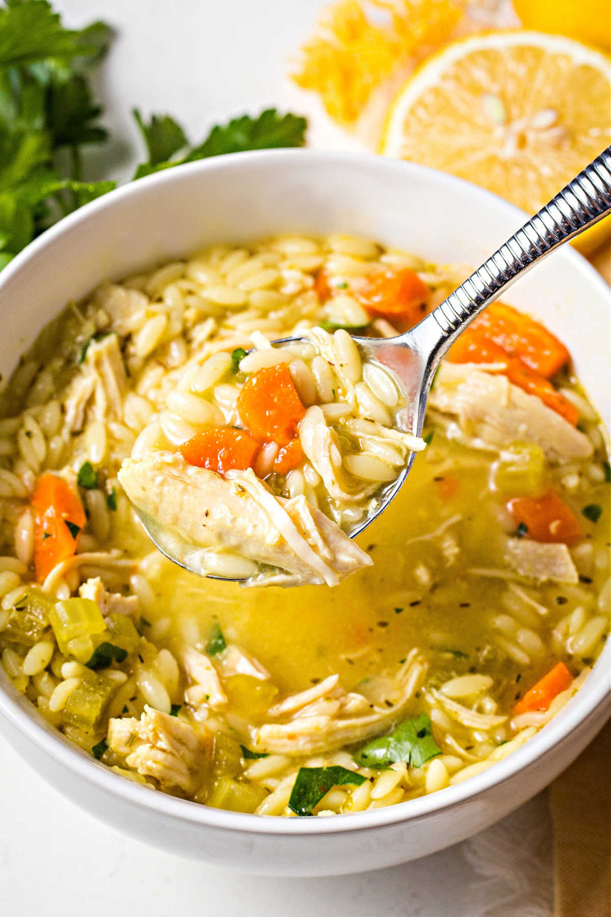 a spoonful of lemon chicken orzo soup coming out of a white bowl on a table.
